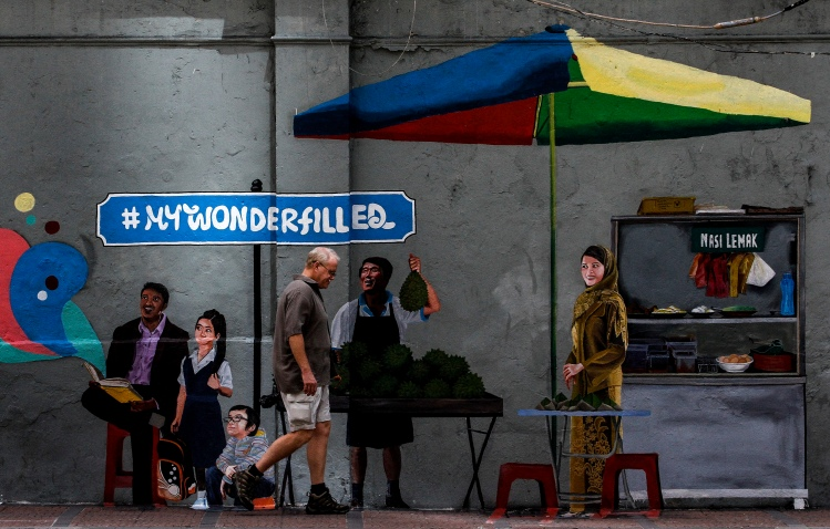 A tourist walks in front of mural on the wall in Kuala Lumpur on December 26, 2015. The Malaysian Insider/Seth Akmal.