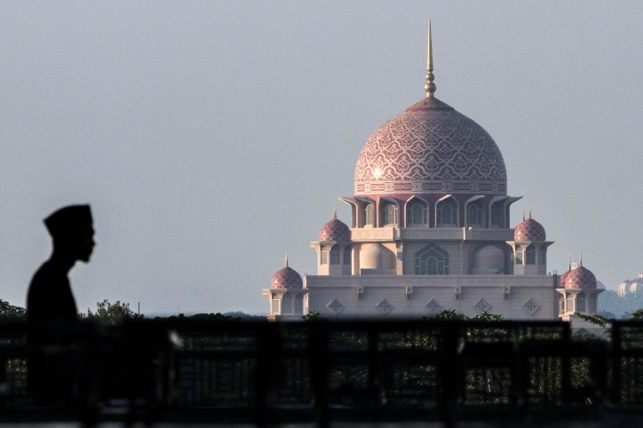 A silhouette of a man is seen walking with a wide background of Masjid Putrajaya, Putrajaya on June 26,2015.-The Malaysian Insider pic by Seth Akmal.