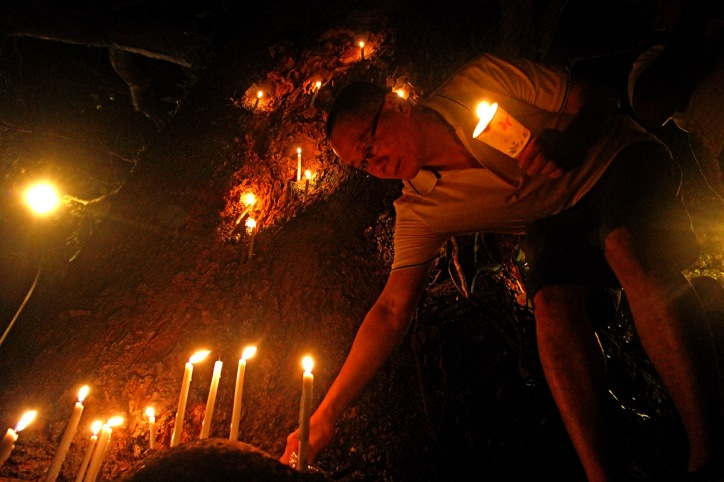 A man put down the candle at the tree decorate with full of candle during candlelight vigil for Nurul Izzah Anwar.