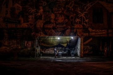 An old man stands under the roof of an abandoned building covered with murals in Kuala Lumpur on May 2, 2016. Picture by Seth Akmal.