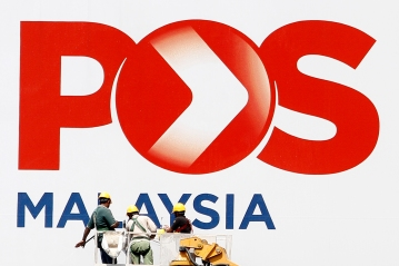 Three workers are seen cleaning Pos Malaysia billboards in Kuala Lumpur on December 25, 2015. The Malaysian/Seth Akmal.