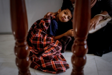 A Rohingya kid is lying down on his mother's thigh while waiting for his turn for circumcision in Selayang, Selangor on April 3, 2016. Picture by Seth Akmal.