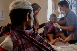 A Rohingya boy looks at his friend getting circumcise after his turn in Selayang, Selangor on April 3, 2016. Picture by Seth Akmal