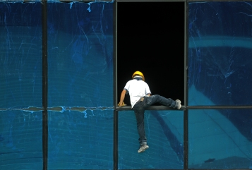 A construction worker climbing on top of the window without safety gear in Kuala Lumpur on 16th April 2015.